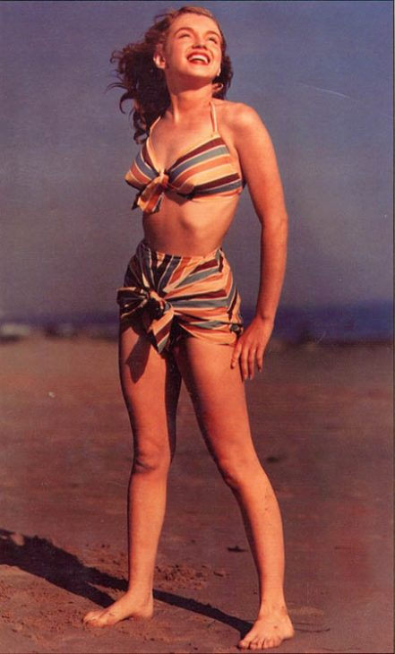 Marilyn Monroe smiles in the sun on a sandy beach, smiling at the sky