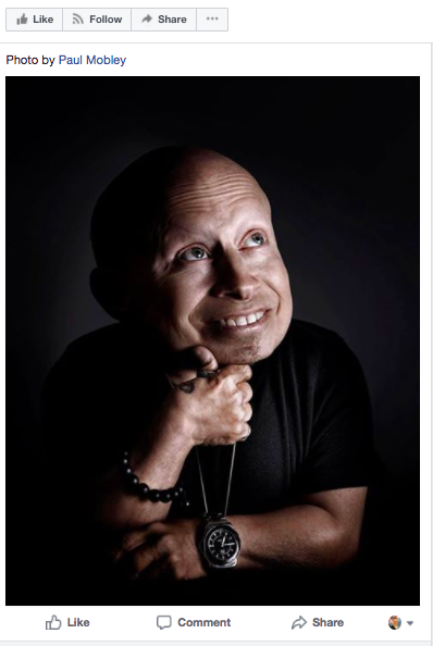 Verne Troyer, bald in a black t-shirt, smiling and looking up