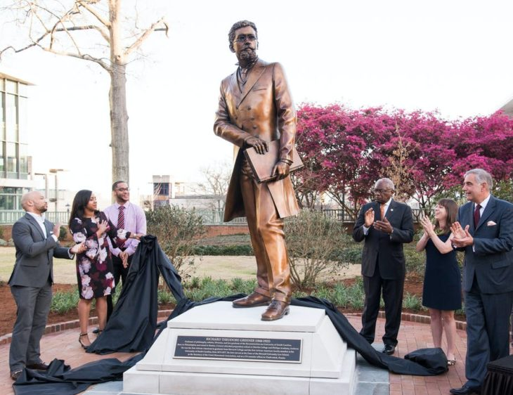 Richard T. Greener statue with people applauding