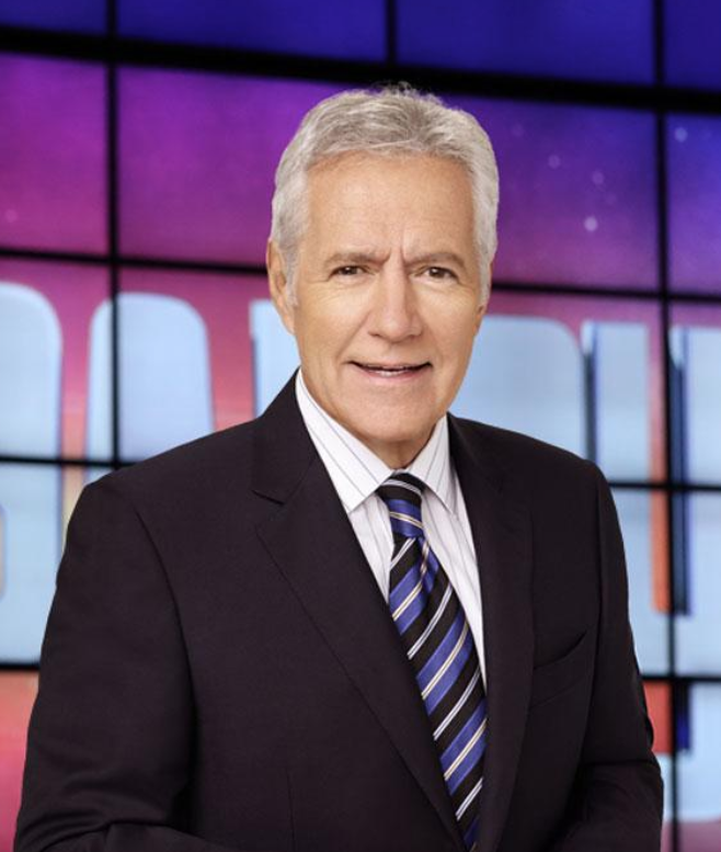 Alex Trebek wears a blue suit and tie, looking good with gray hair on the colorful set of 'Jeopardy!'