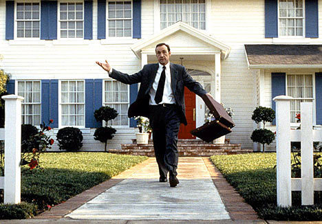 Photo of Kevin Spacey walking out of a suburban home with a white fence in 'American Beauty'