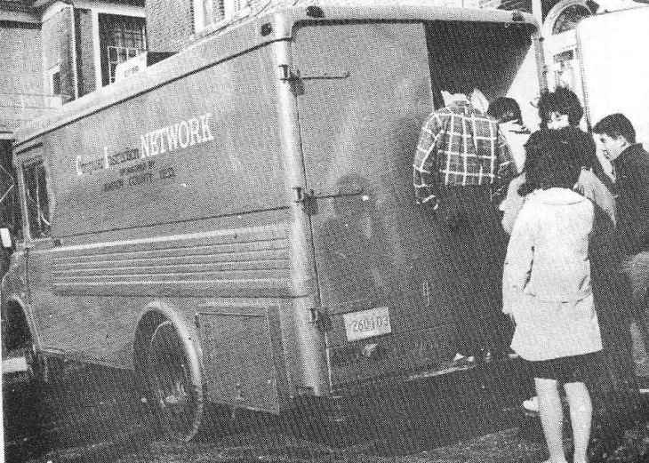 A photo of an old van with students lined up at the back and the words 'Computer Instruction Network' on the side