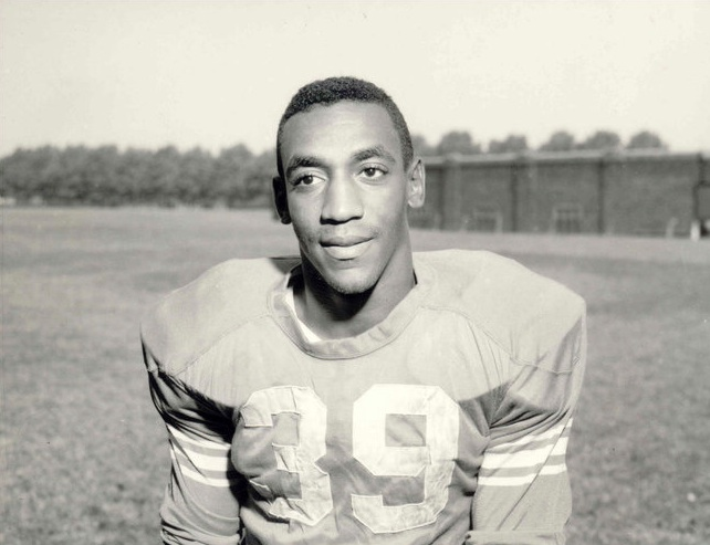 A very young Bill Cosby wears an old-fashioned football jersey, number 39, as he stands on a practice field