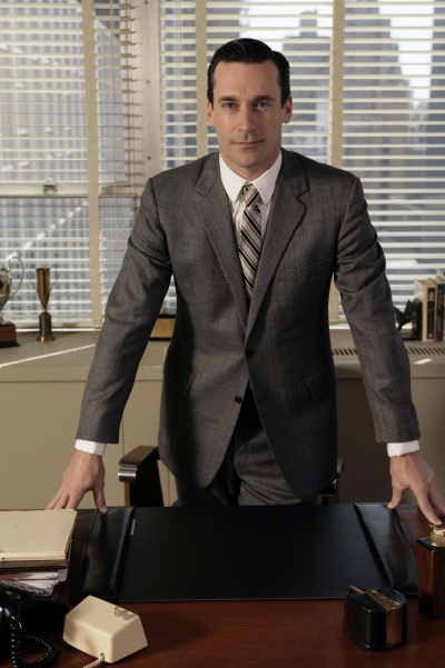 A photo of Don Draper in his office, hands on desk, half-smiling at the camera