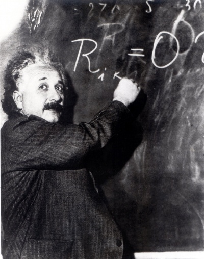 A photo of Albert Einstein at a chalkboard, writing an equation and looking back at the room