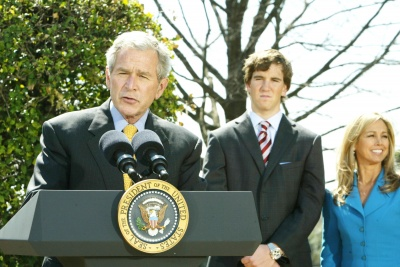 President Bush speaks at an outdoor podium while Eli Manning listens behind him