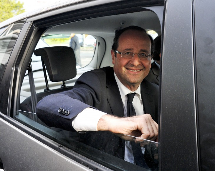 A photo of Francois Hollande, smiling as he leans out the window of his black limousine