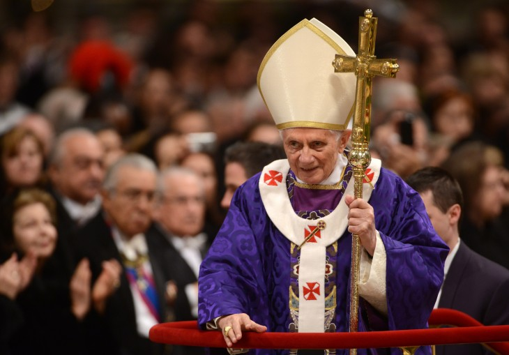 Photo of Benedict XVI in purple robe in a big cathedral, leaning on his staff
