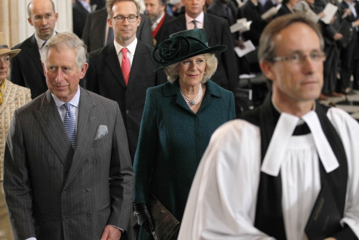 Photo of Prince Charles and Camilla in church dress, walking in a procession behind some bishops or clergy of some kind