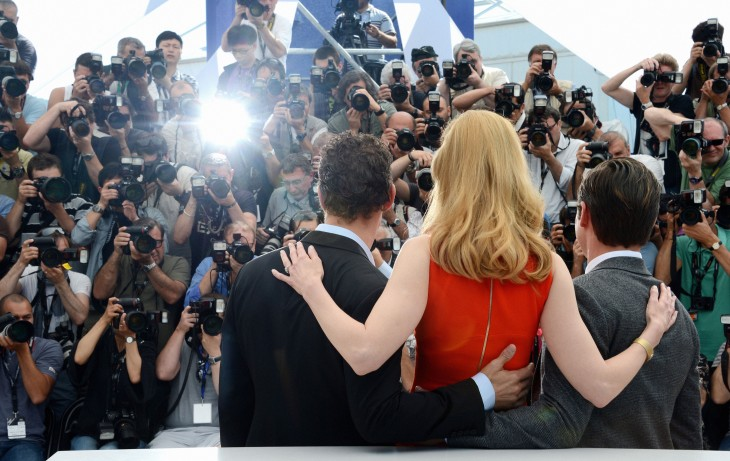 Photo of Nicole Kidman at Cannes, from behind, posing for a bank of photographers with her arms around two men