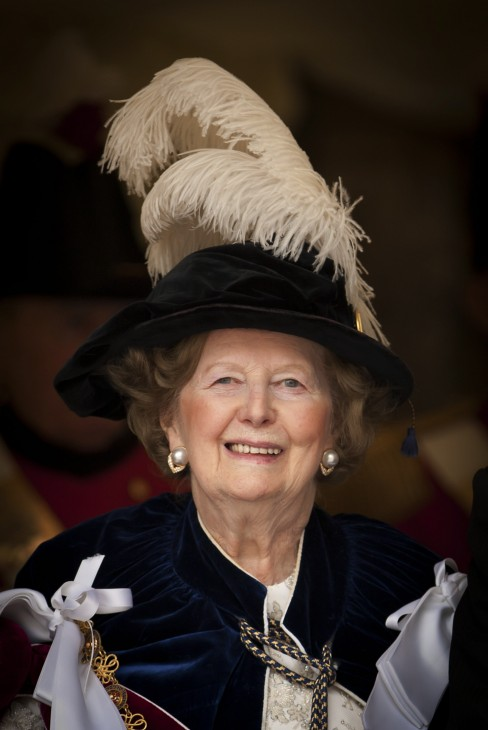 Margaret Thatcher photo with a large feather in her hat and an academic gown, smiling