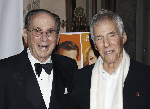 Photo of Hal David, balding and in a tux, with a wan-looking Burt Bacharach in a fancy scarf