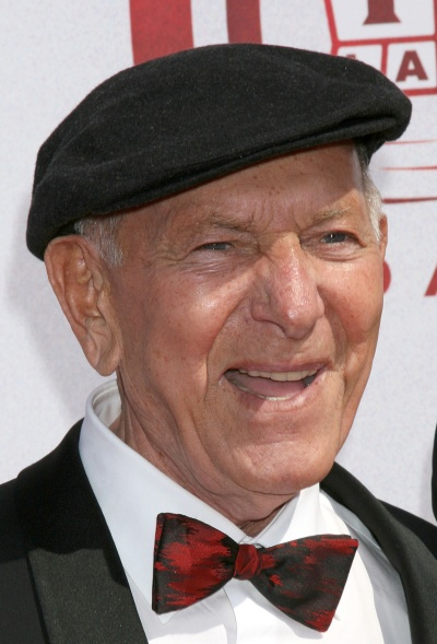 A photo of Jack Klugman in a bow tie and beret-type cap, grinning for cameras