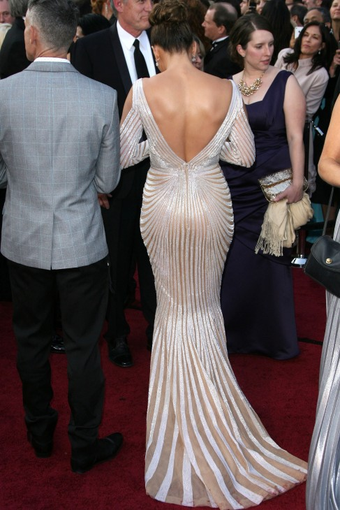 Photo of Jennifer Lopez from the back in a shimmering ivory Oscar gown