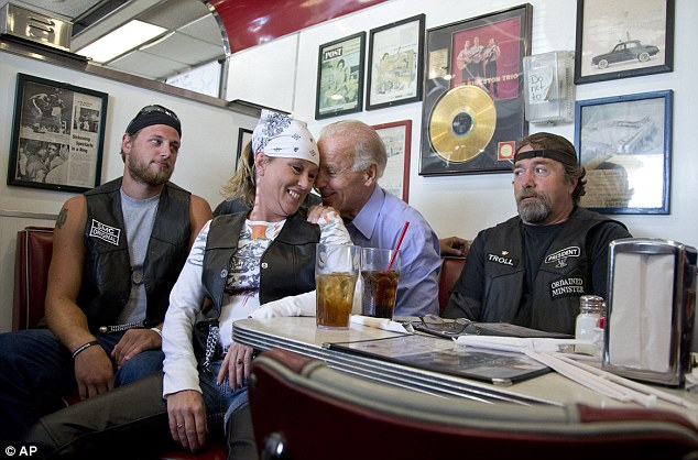 Photo of Joe Biden with a biker chick in his lap (actually in a chair in front of him) in a diner