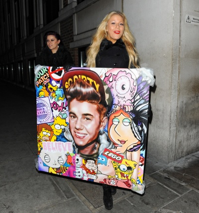 A youngish blonde Justin Bieber fan carries a weird painted collage of Bieber plus the Legos logo and scenes from 'Family Guy'