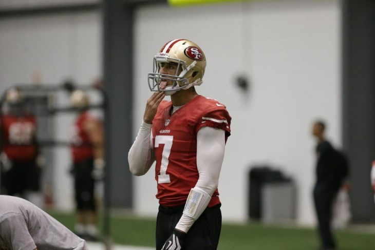 Photo of Colin Kaepernick licking his fingers as he prepares to take a snap at practice