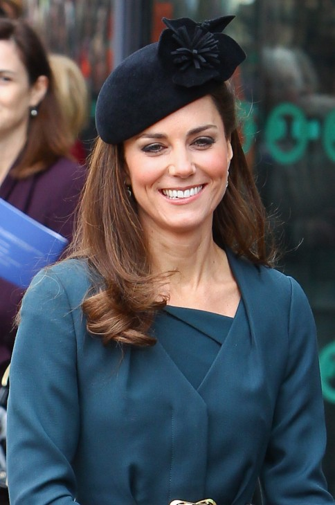 Photo of Kate Middleton in stylish black hat and green wraparound sweater
