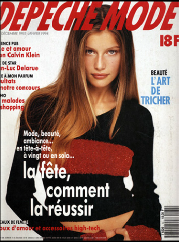 Magazine cover of Laetitia Casta in a short sweater, looking solemnly at the camera with long brown-blonde hair