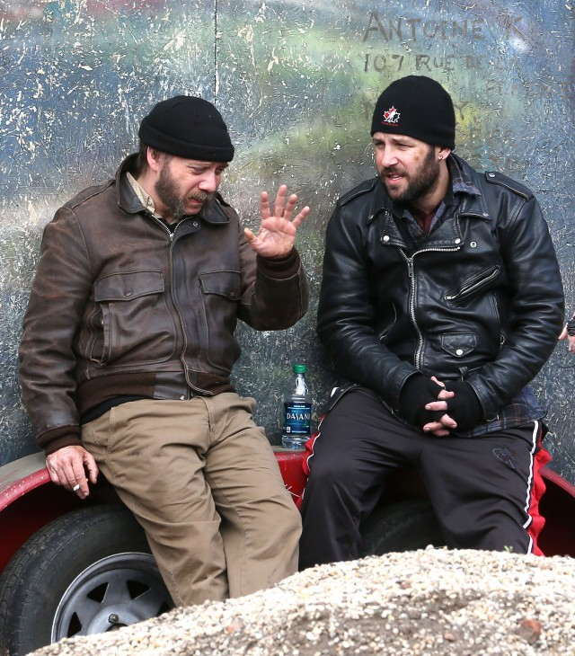 Photo of Paul Giamatti waving his hand as he talks with Paul Rudd, leaning on a trailer bumper