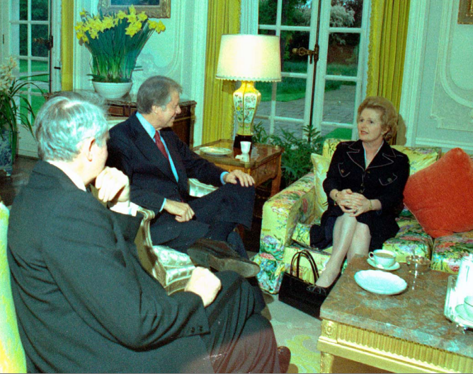 Photo of Margaret Thatcher on a flowery couch in a sitting room, chatting with Jimmy Carter and Cyrus Vance