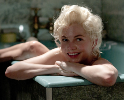 Michelle Williams in a tub, smiling, as Marilyn Monroe