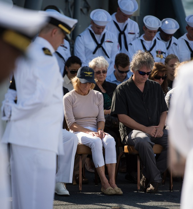 A photo of Neil Armstrong's wife and his son, sitting on deck with heads bowed