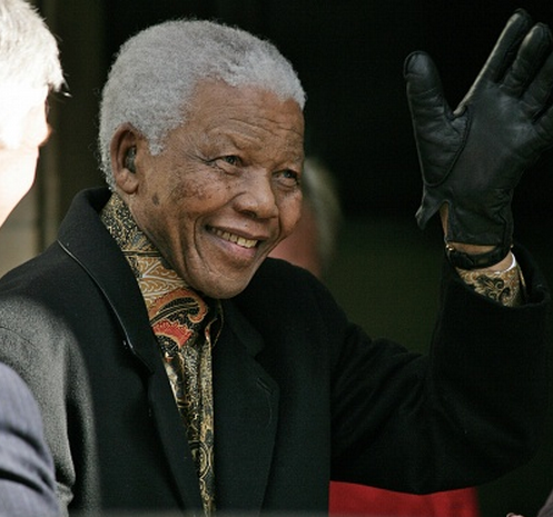 Photo of Nelson Mandela in coat and gloves, smiling and waving