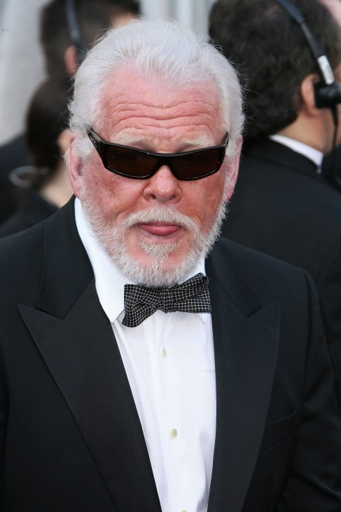 Photo of Nick Nolte, in a tuxedo and sunglasses, looking a little scary with his tongue half out