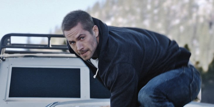 Paul Walker, face grizzled, prepares to leap from a moving car