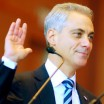 Rahm Emmanuel's missing finger is really the top half of his middle finger, cut off between the second and third knuckle. He stands in a blue suit and tie, surrounded by family, as he raises his hand to take the oath of office.