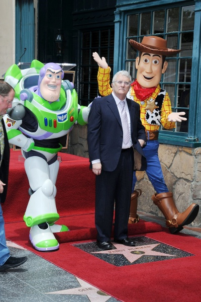 Randy Newman walks on a red carpet with people dressed as 'Toy Story' characters