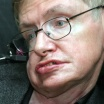 Photo of Stephen Hawking, in wire-frame glasses, his eyes bright but face twisted and distorted by ALS