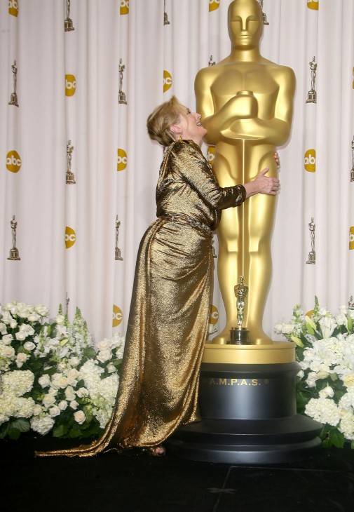 Photo of Meryl Streep hugging a huge statue of Oscar
