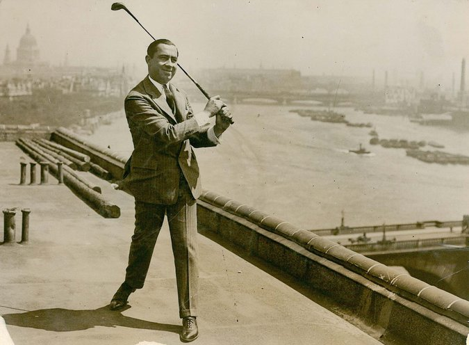 Walter Hagen stands on a rooftop, dressed in a full business suit, swinging a golf club