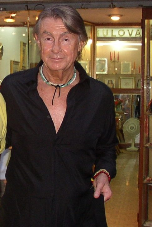 Joel Schumacher looks disheveled and sweaty, as if caught by surprise on a day off, as a fan snaps a photo