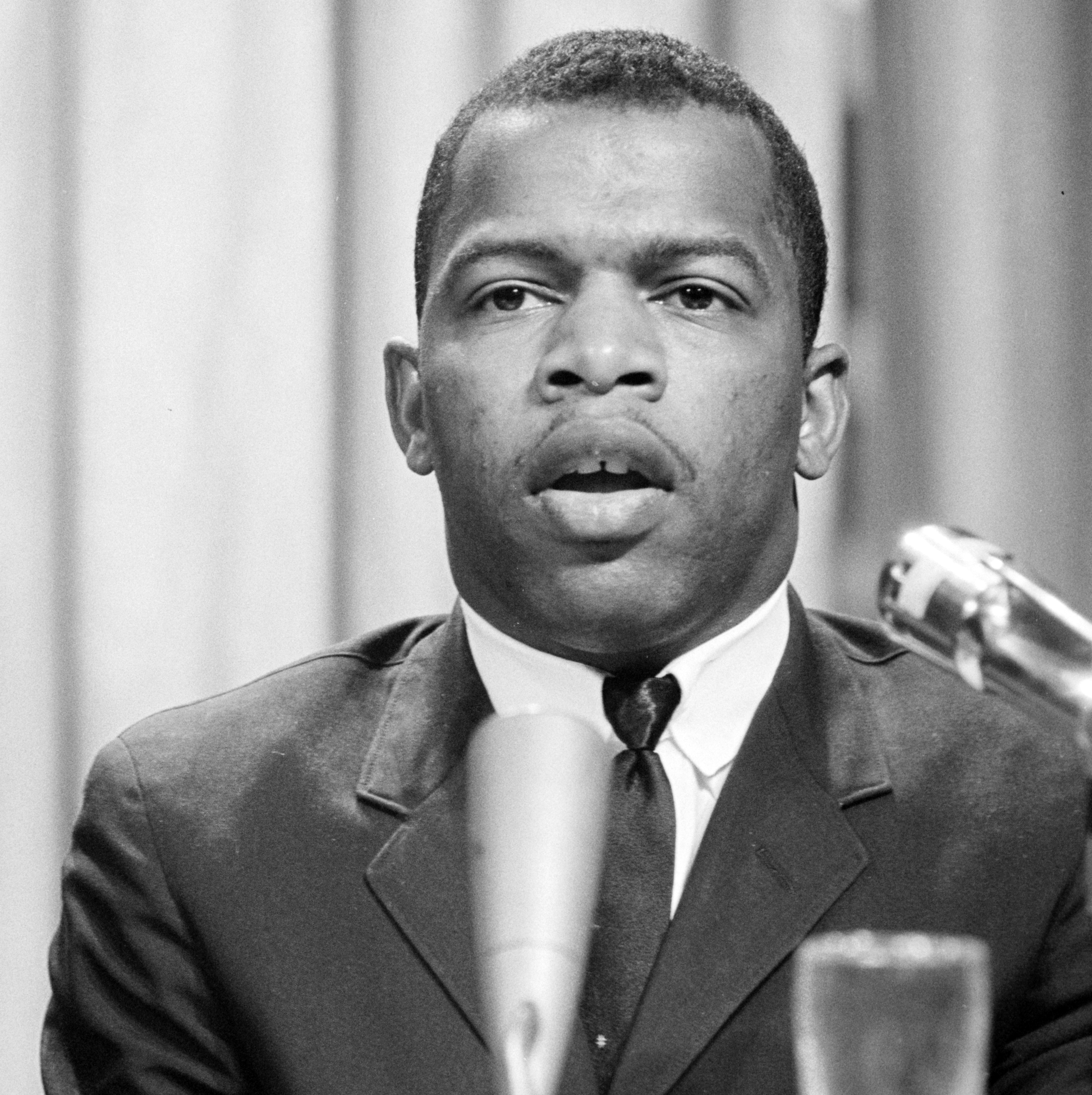 John Lewis, wearing a dark suit and tie, speaks behind a lectern in front of a rather bland gray backdrop