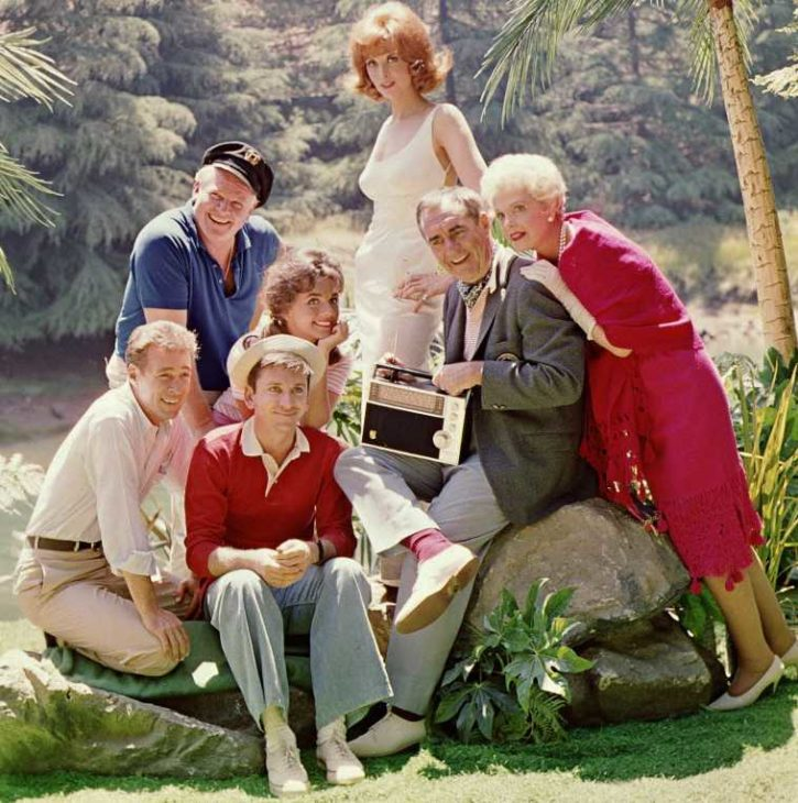 Seven people in casual dress sit and stand around a tree trunk on an (alleged) tropical island